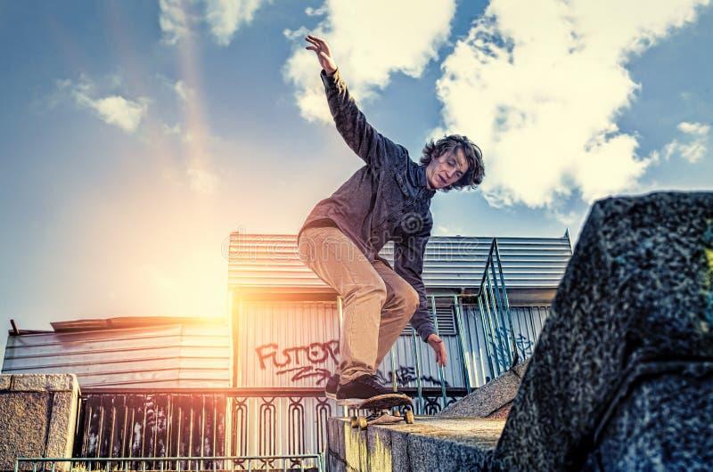 Planchiste faisant un tour sautant de planche à roulettes à la ville de lever de soleil photographie stock libre de droits