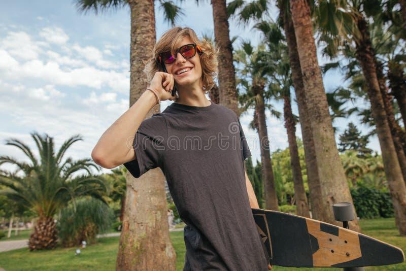 Planchiste marchant avec le longboard à disposition et le téléphone parlant images stock