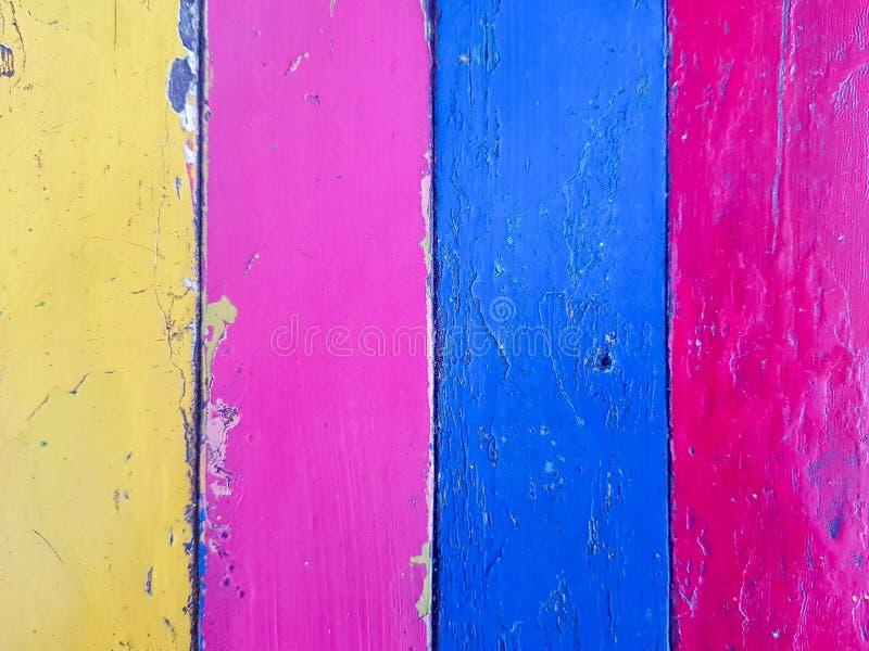 Plancia di legno dipinta con colore giallo, rosa, blu e rosso variopinto nel modello delle bande fotografia stock libera da diritti