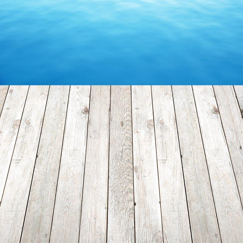 Plancia di legno sul fondo dell'acqua blu immagini stock libere da diritti