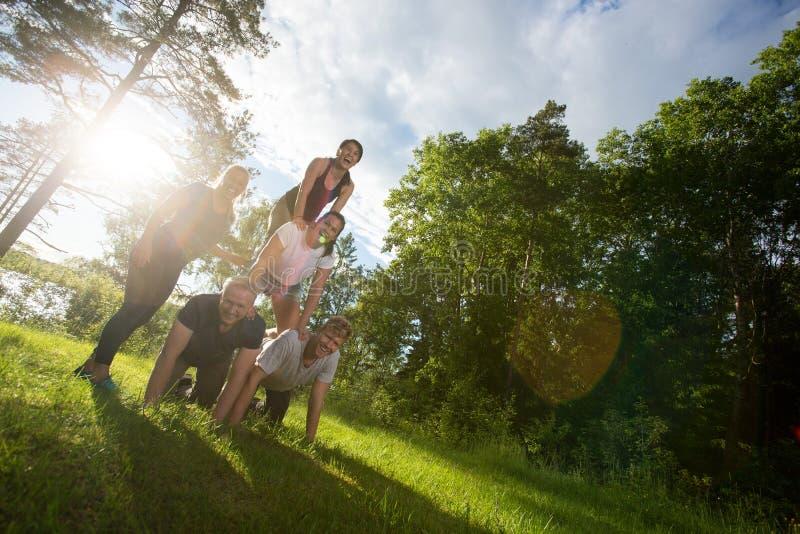 Plandeka wizerunek Szczęśliwi przyjaciele Robi Ludzkiemu ostrosłupowi W lesie obrazy stock