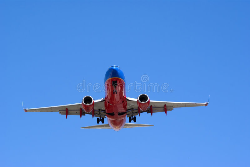 Plane. Commercial plane landing with blue sky royalty free stock image