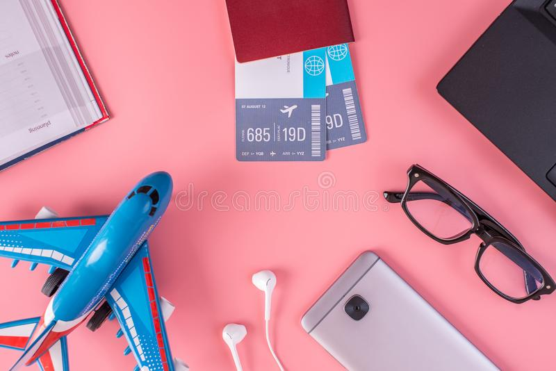 Plane, air tickets, passport, notebook and phone with headphones on pink background. The concept of planning for travel. Plane, air tickets, passport, notebook stock photo