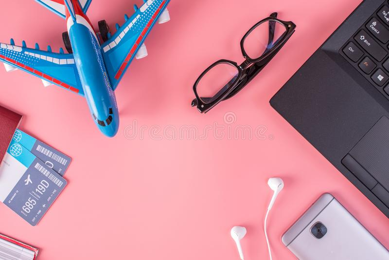Plane, air tickets, passport, notebook and phone with headphones on pink background. The concept of preparing for travel. Plane, air tickets, passport, notebook royalty free stock photography