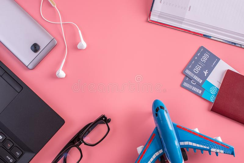 Plane, air tickets, passport, notebook and phone with headphones on pink background. The concept of preparing for travel. Plane, air tickets, passport, notebook stock images