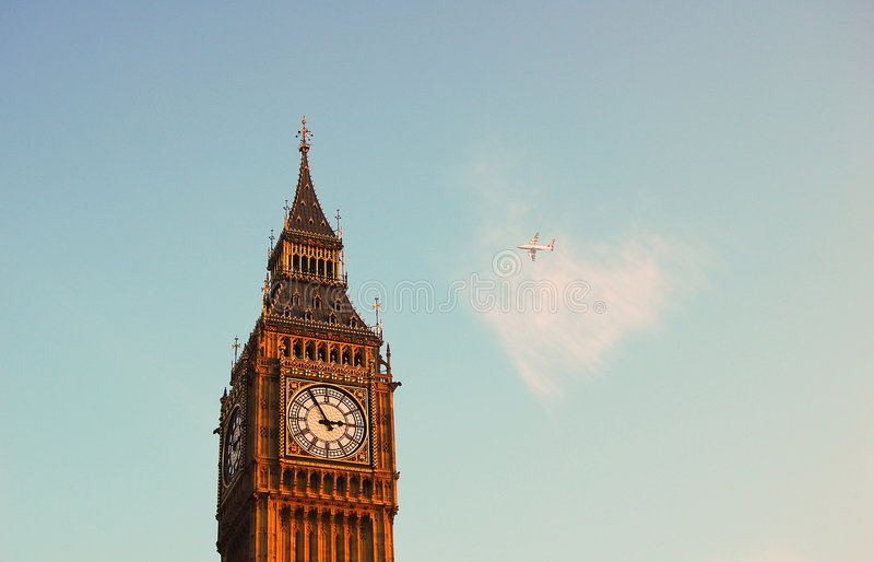A plane by the Big Ben. Commercial airplane flying behind the Big Ben in London, England royalty free stock photo