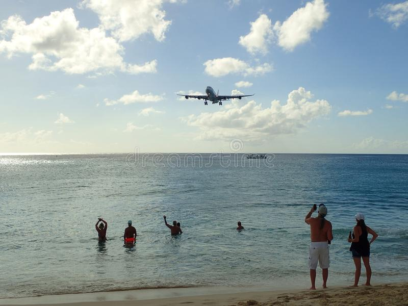 A plane is descending towards Princess Juliana International Airport SXM over the beach.  stock photography
