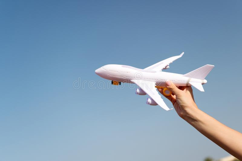 Plane in female hand clear blue sky background copy space. Travel and vacation. Book tickets now. Toy white plane fly. Vacation destinations. Travel comfortable stock photos