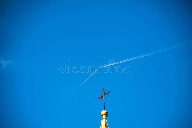 The plane flies in the blue sky, leaving a white trail. The dome of the church. stock photography
