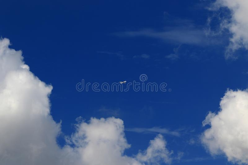 A plane fly on blue sky and white cloud. royalty free stock images