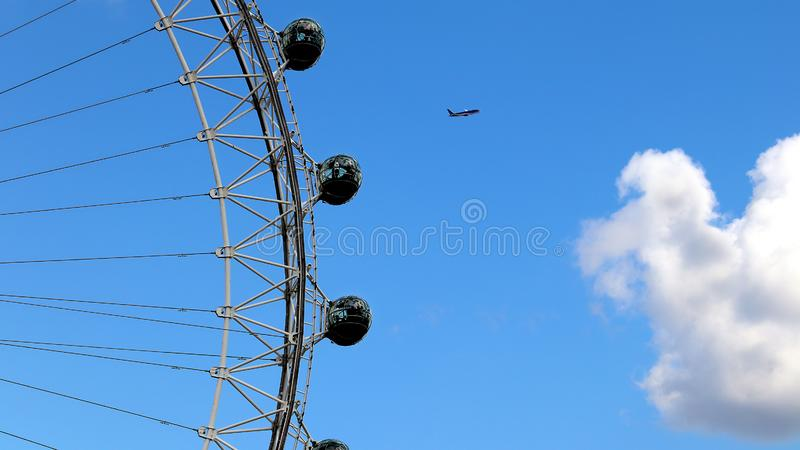 Plane above London Eye. A plane flying above the London Eye in England with a white fluffy cloud stock image