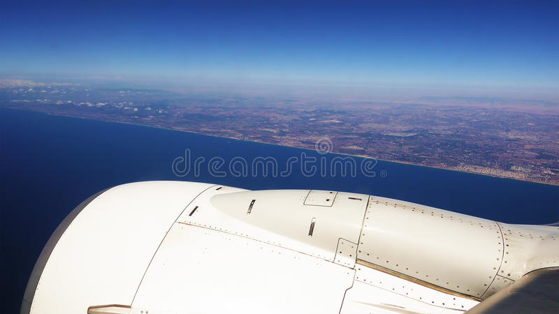 Plane is flying along the sea coast after takeoff stock image