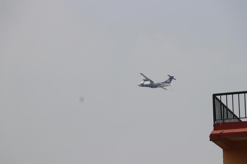 Plane flying at near land. see right above the balcony of house stock images