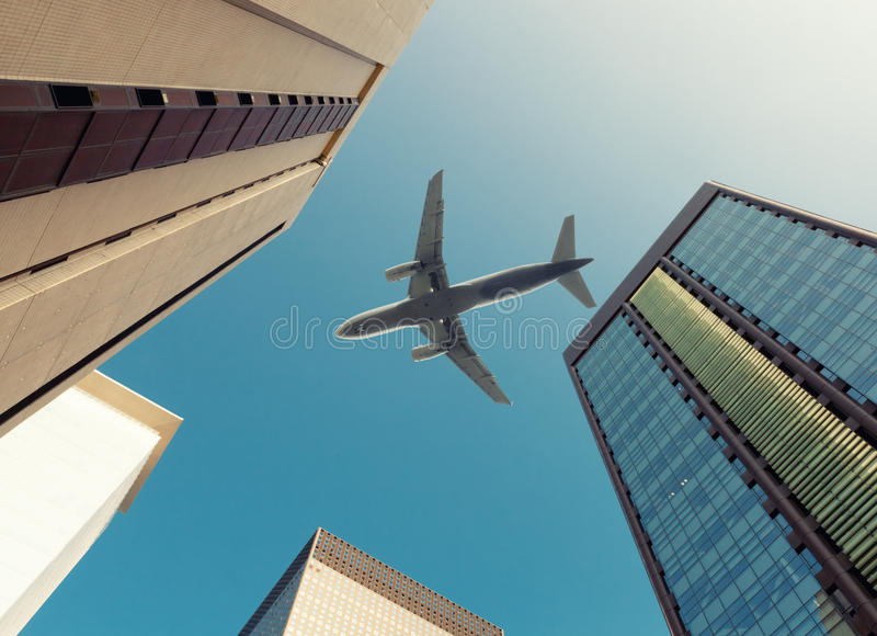Plane flying over a business skyscrapers filled with offices stock photos