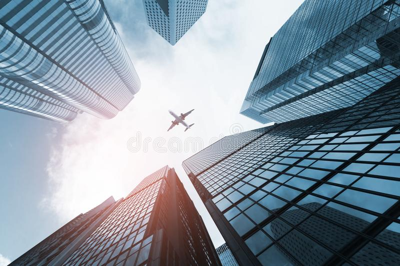 Plane flying over business skyscrapers royalty free stock photography