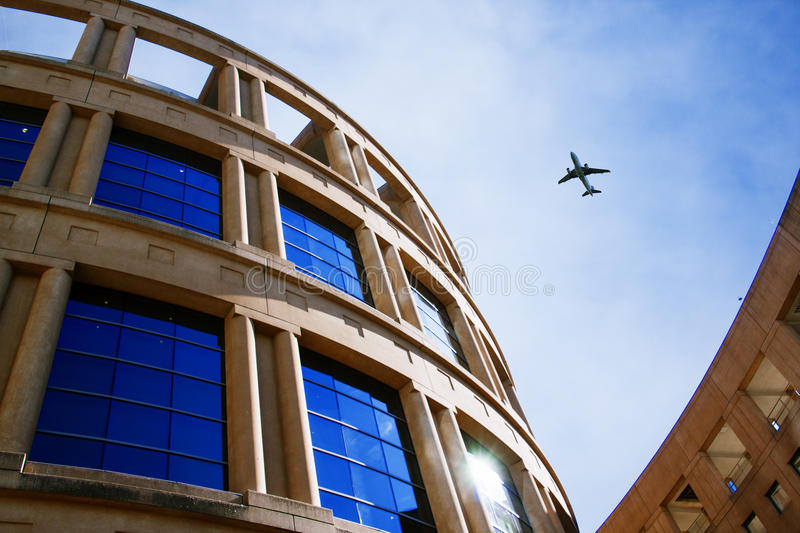 Plane flying over curvy building stock image