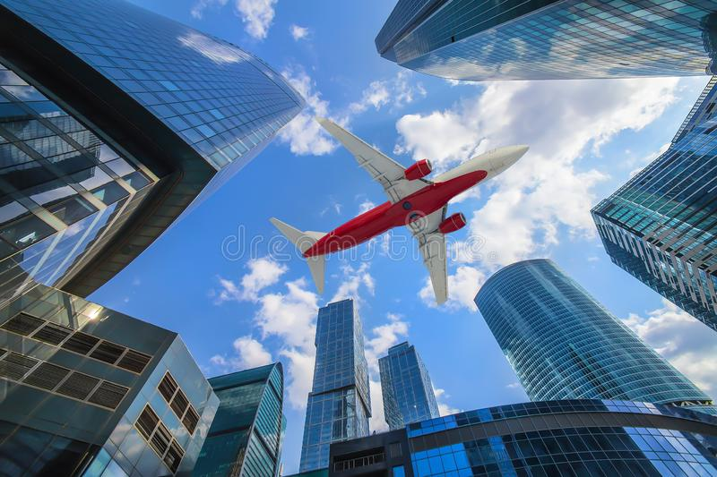 plane flying over high buildings of business center stock photography