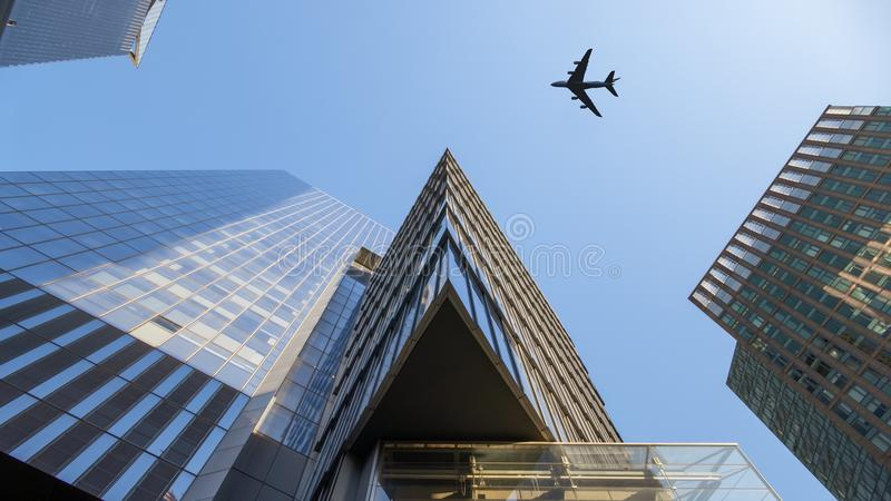 a plane flying over modern buildings of New York City royalty free stock photos