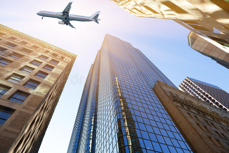 Plane flying over skyscrapers stock images