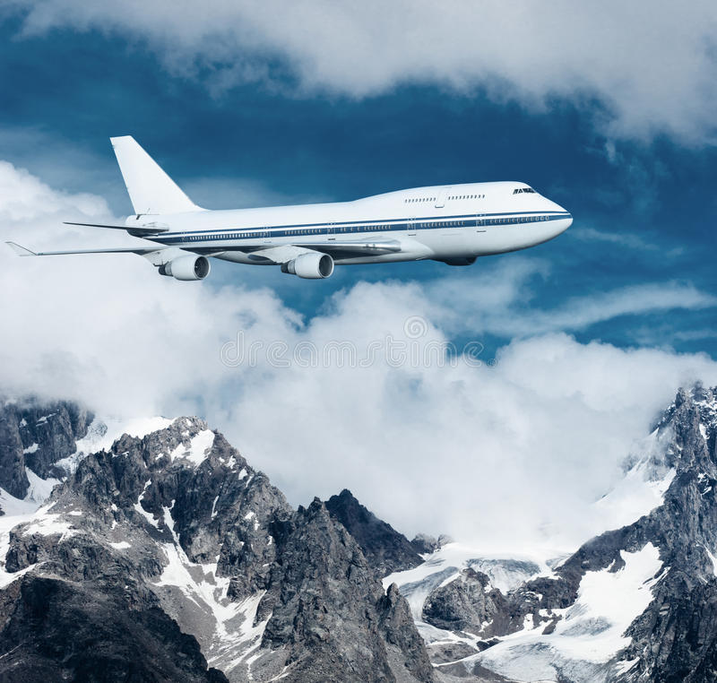 Plane flying over the snow-capped mountains. royalty free stock photography