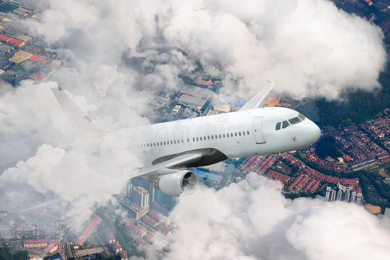 Plane flying sky. Airplane above city. White passenger aircraft climbs through the clouds. royalty free stock images