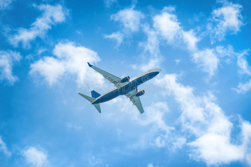 A plane flying in the sky. A plane flying in the blue sky with white clouds stock images