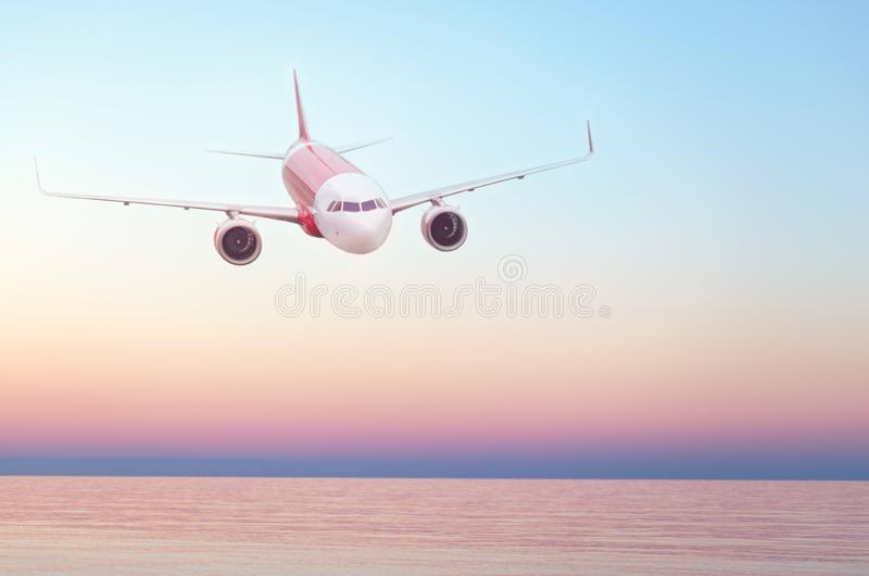 Plane flying in the sky, summer travel flight, airplane over water, flight over skyline. Sunset over the sea. Empty place for text, copy space royalty free stock images