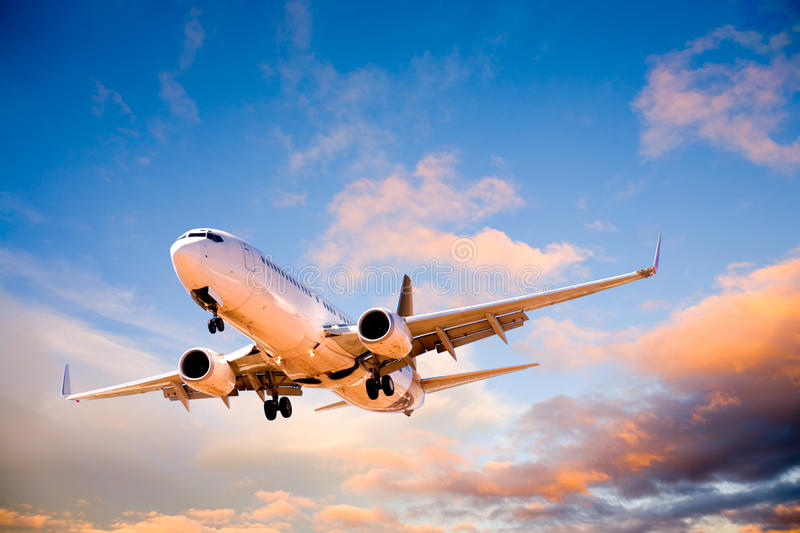 Plane Flying in Sunset Sky royalty free stock photography