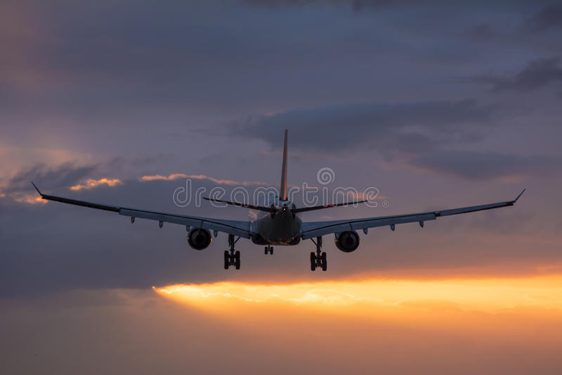 Plane flying towards the runway during a cloudy sunrise. stock photo