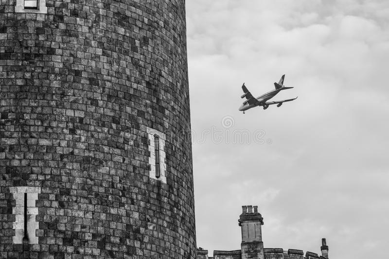 Plane flying by the town of Windsor b/w. There will be many people flying into the London airports servicing the city of Windsor this week for the royal wedding royalty free stock photos