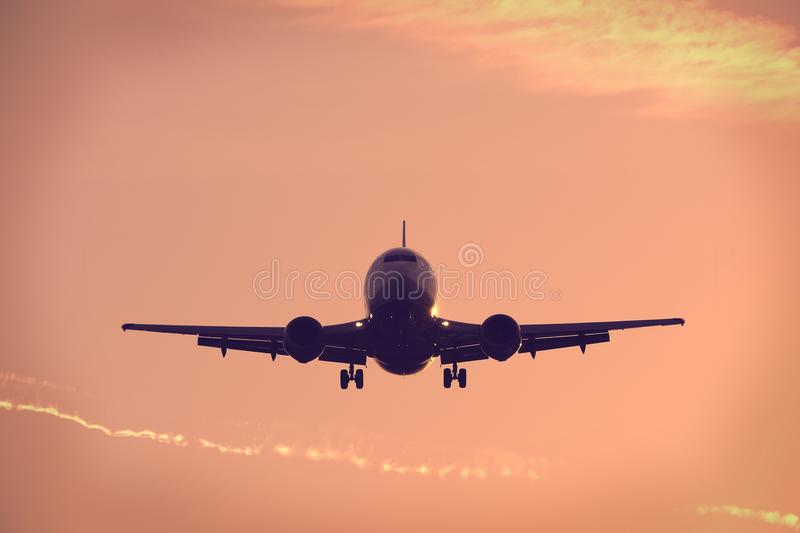 Silhouette of plane flying up in the blue sky, landing royalty free stock images