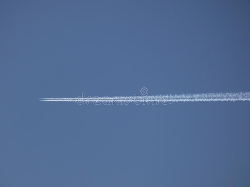 Plane furrowing the blue sky royalty free stock images