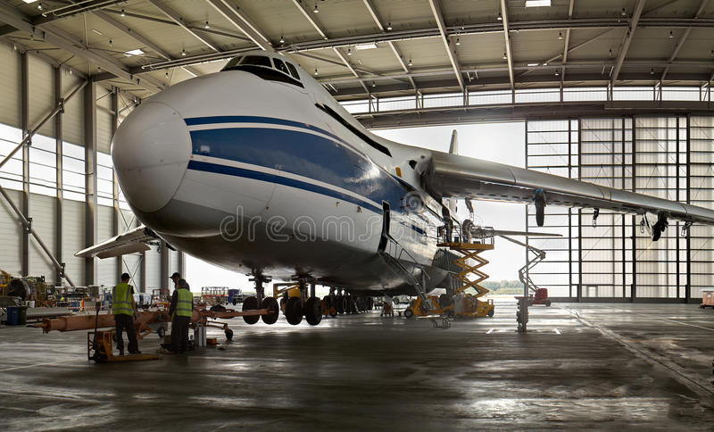 The plane in the harbor-the world`s largest Russian cargo plane Ruslan and the people working on it royalty free stock image