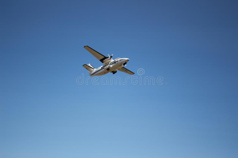 The plane hovering in the blue sky. royalty free stock images