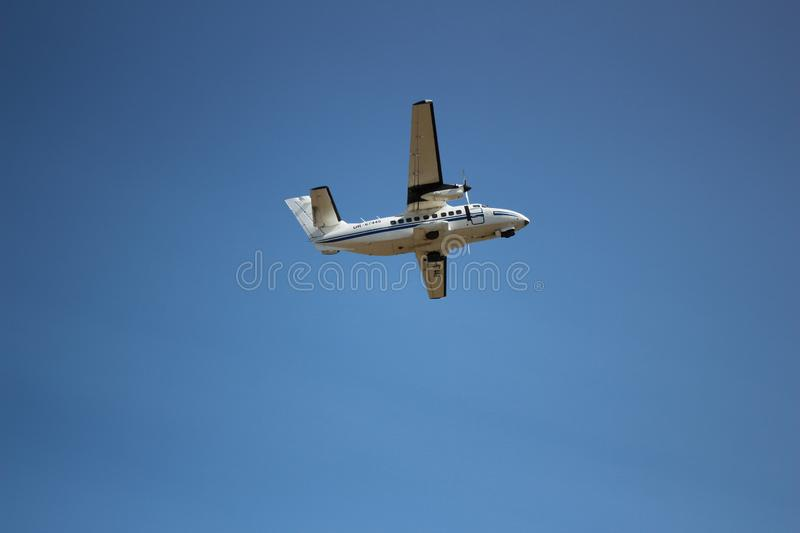 The plane hovering in the blue sky. Passenger and cargo air transportation. airman. turns stock photography