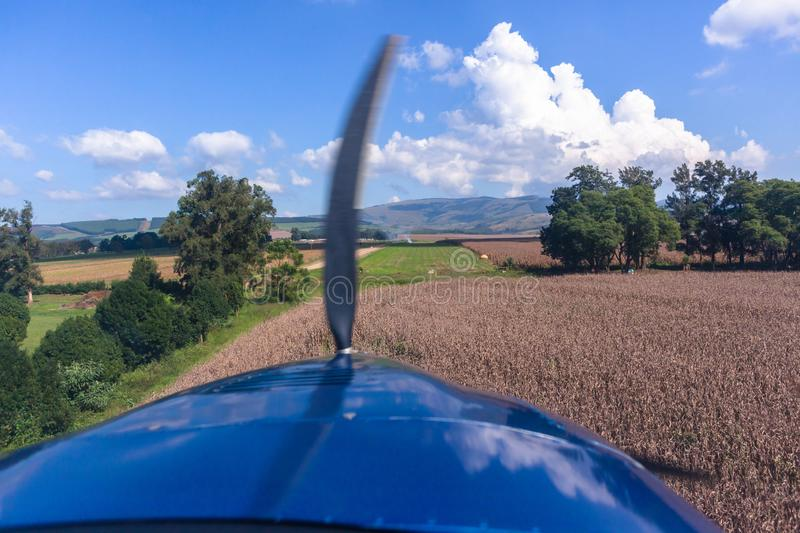 Plane Pilot View Landing Approach Grass Runway. Pilots cockpit landing approach view in light propeller aircraft plane in rural farming countryside over maize royalty free stock photo