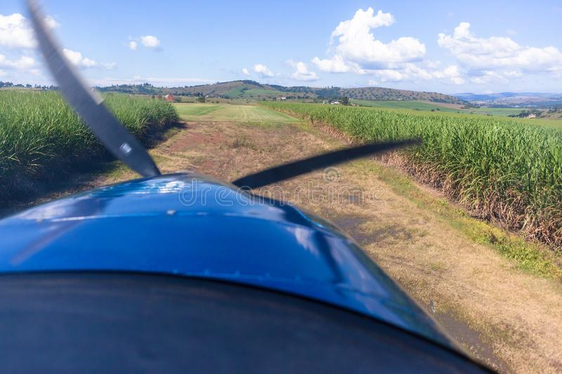 Plane Pilot View Landing Approach Grass Runway. Pilots cockpit landing approach view in light propeller aircraft plane in rural farming countryside over maize royalty free stock images