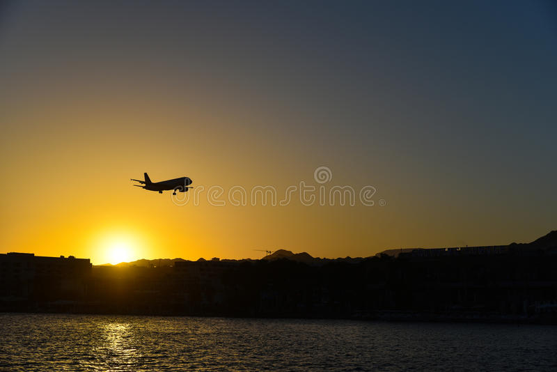 Plane landing over the city of Eilat at sunset. Plane landing at sunset to the airport of Eilat, Israel. The Eilat airport is used for internal flights only stock photography