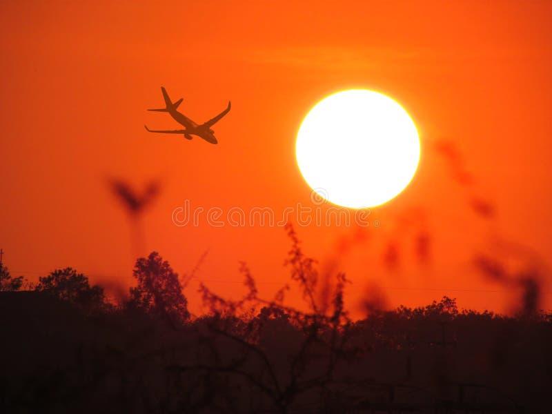 Plane landing over setting sun background stock photos
