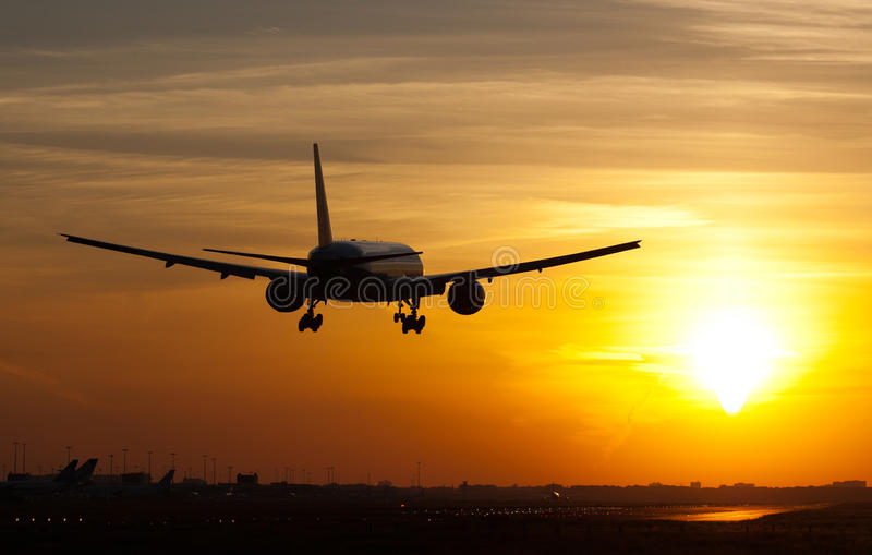 Plane landing in sunrise stock images