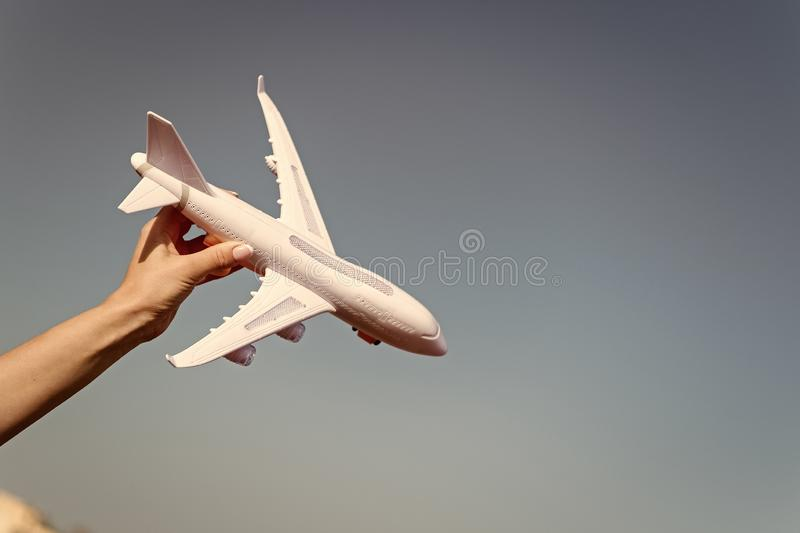 Plane model in hand. Airplane on blue sky. Jet or aircraft toy on sunny outdoor. Travel by air transport, aviation. Symbol of wanderlust, trip and vacation royalty free stock photo