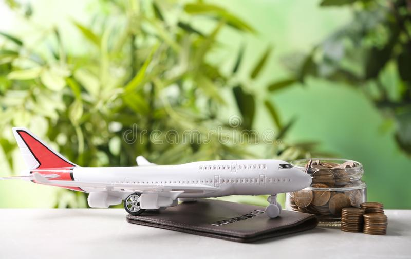 Plane model, passport and coins on table against blurred background. Space for text stock photography