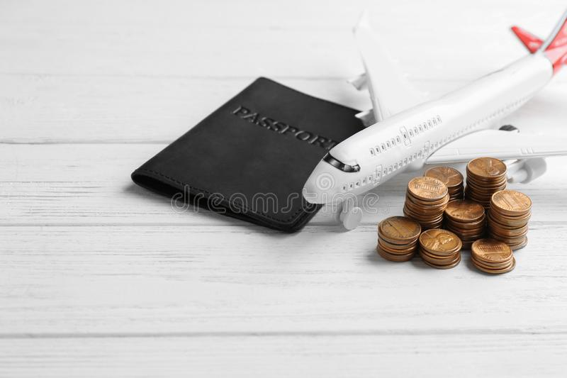 Plane model, passport and coins on white wooden background. Space for text royalty free stock photos