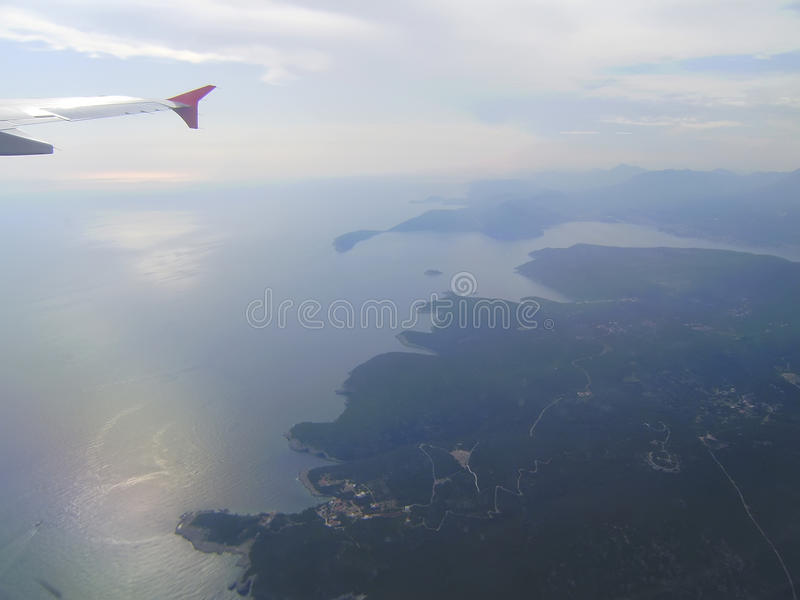 the plane over the city and the sea royalty free stock image