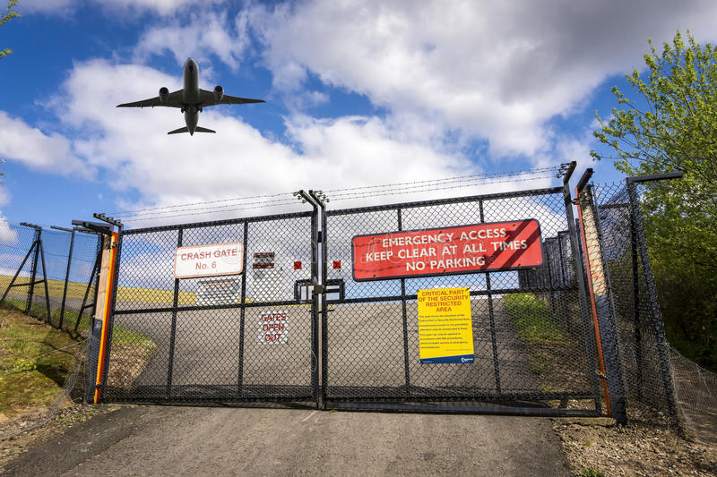 Plane over gates of Manchester Airport, England. Airplane flying over gates on roadway at Manchester Airport, England on sunny day stock images