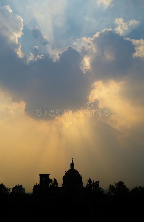 Plane passing flying over a building church and the clouds with a ray of light stock image