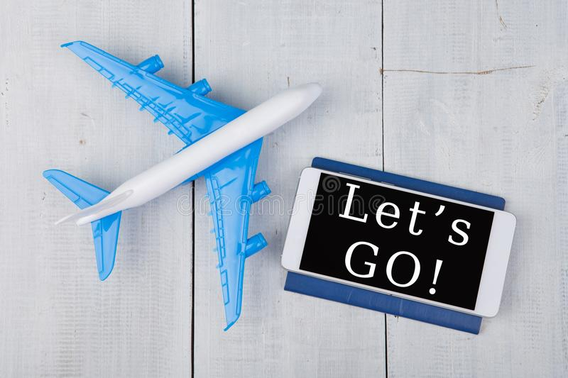 plane, passport and smartphone with text & x22;Let& x27;s go!& x22; royalty free stock photography