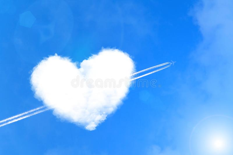 The plane pierces a cloud of heart like an arrow of cupid. Valentine`s Day Concept royalty free stock photos