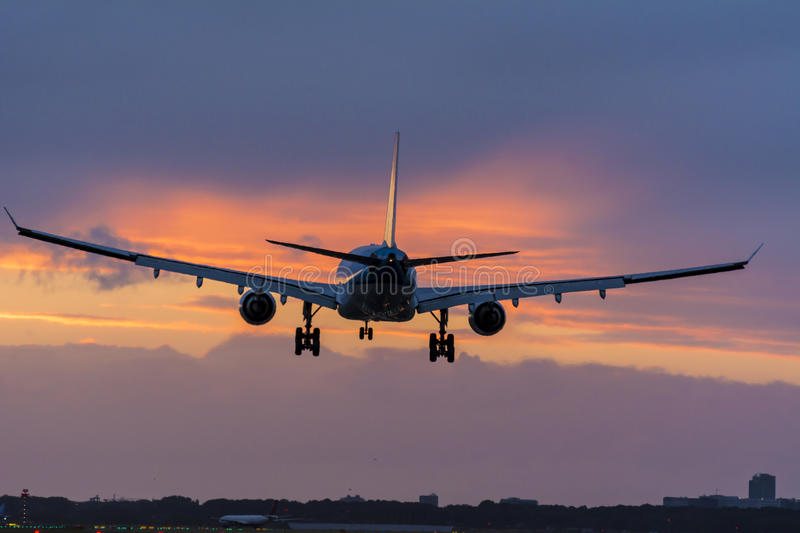 Plane is preparing for landing at the runway. Shot taken couple minutes before a nice cloudy sunrise. stock images
