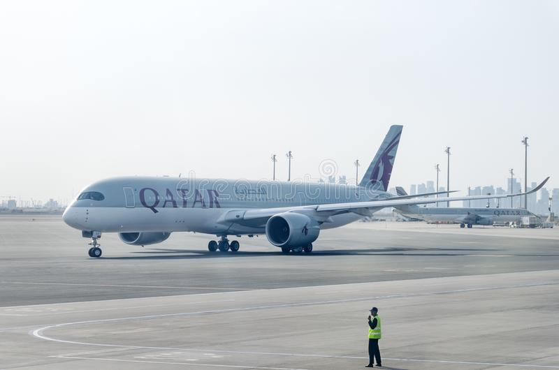 Plane by Qatar Airlines leaves the parking lot. Marshaller controls the movement of the aircraft. stock image